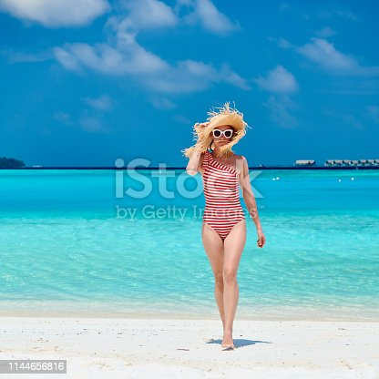 Woman in one-piece swimsuit walking at tropical beach with white sand. Summer vacation at Maldives.