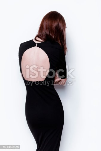 Attractive young woman with simple hairstyle wearing beautiful open back black dress. Back view. Fashion model studio portrait on white background.