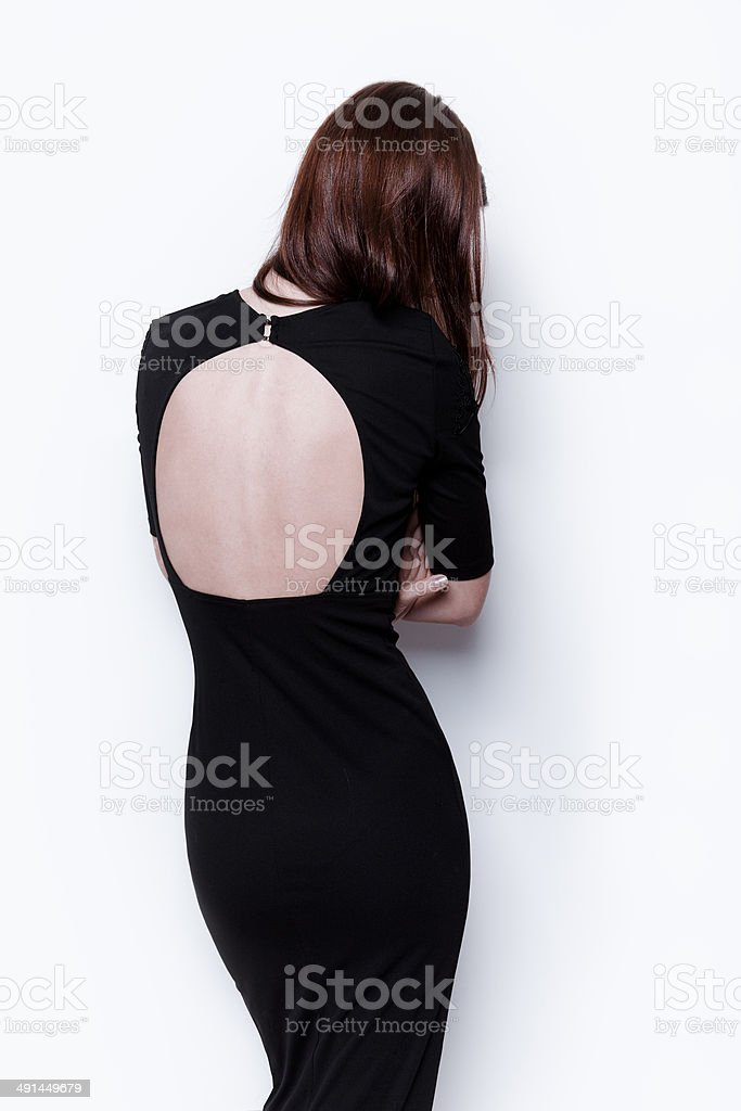Woman in open back black dress stock photo