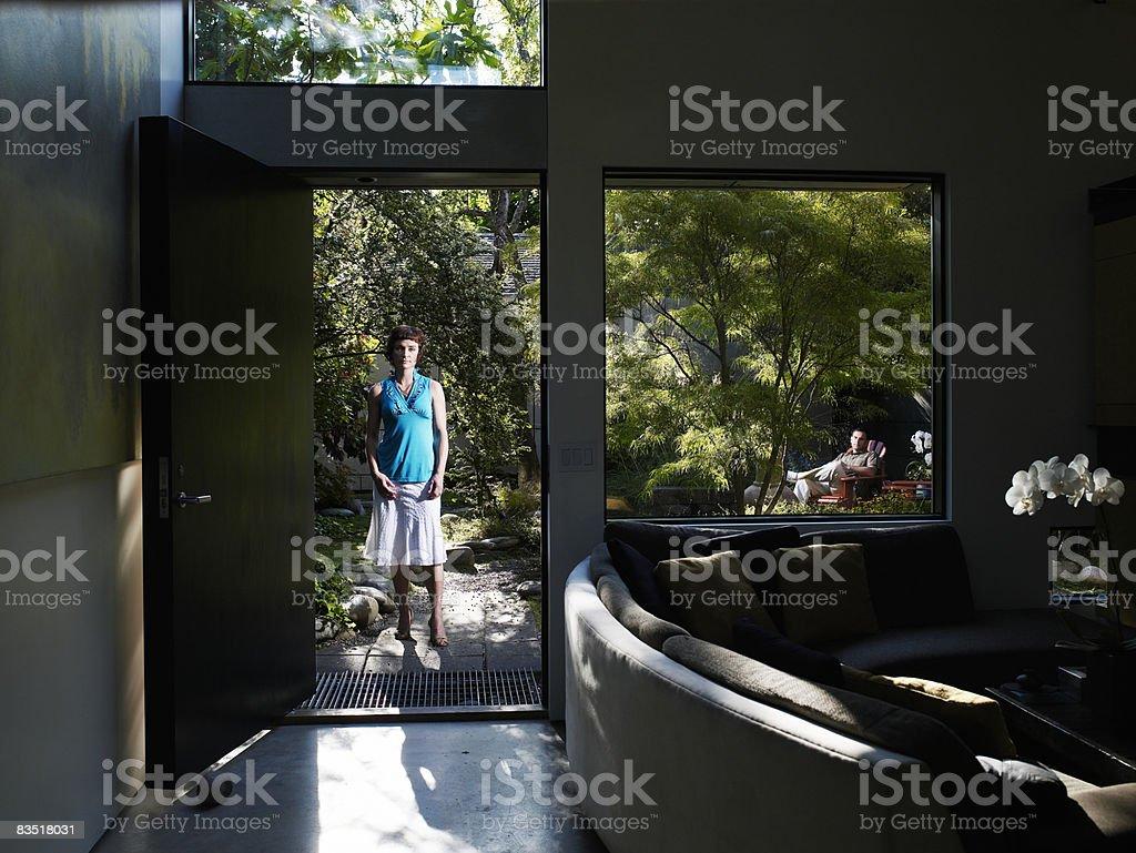 Woman in open doorway, husband in background royalty free stockfoto