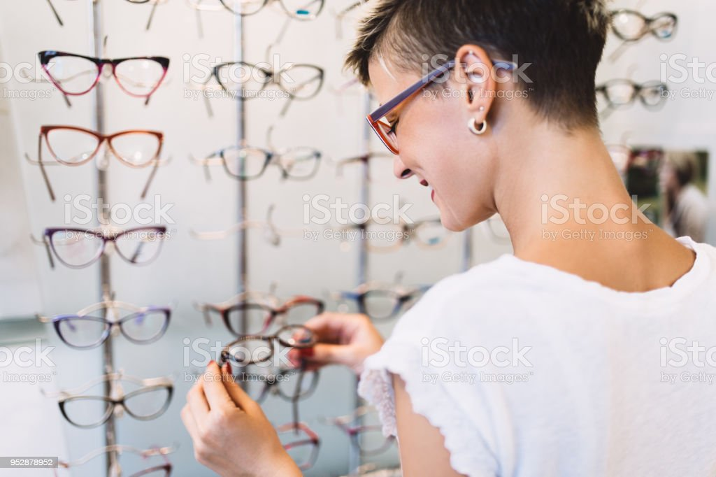 Beautiful middle age woman choosing a glasses in optician store.