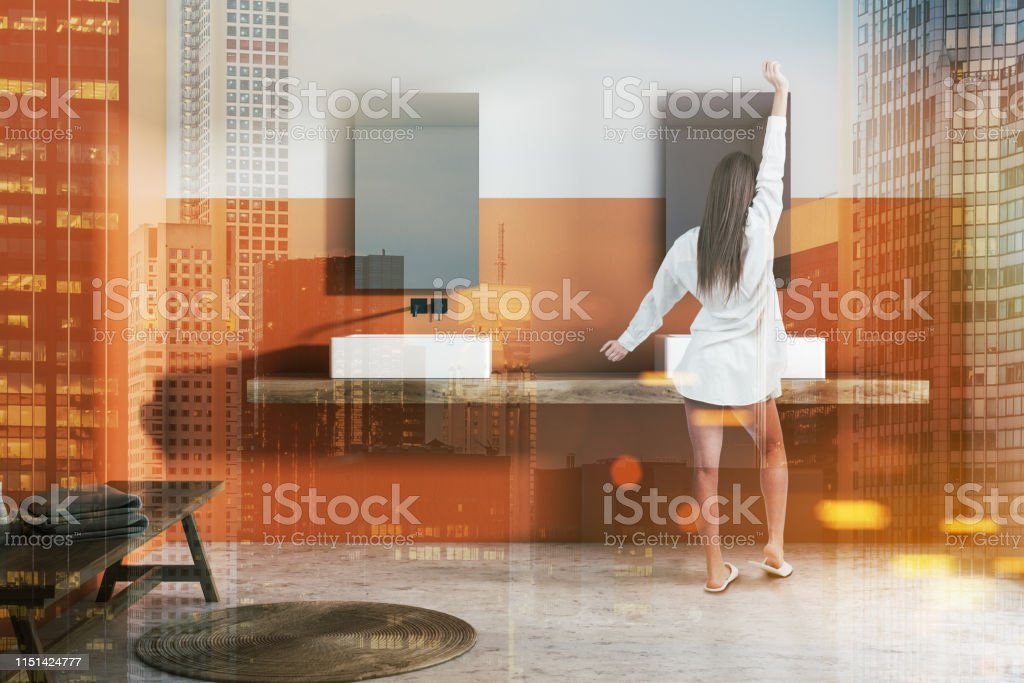 Woman in interior of modern bathroom with white and orange walls,...