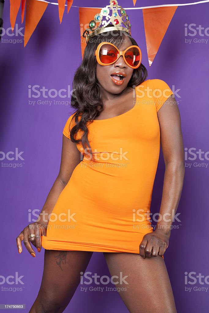 Woman in orange dress with crown stock photo