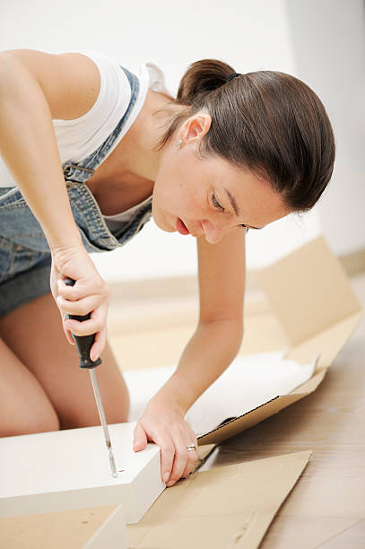 Woman in overalls assembling flat pack furniture stock photo
