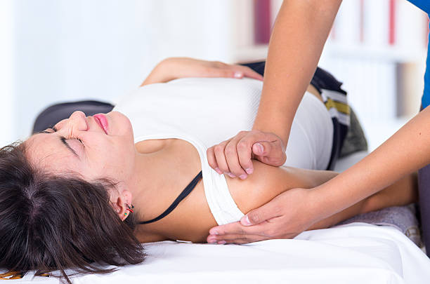 woman in pain lying while getting a shoulder massage concept young woman in pain lying while getting a massage from specialist concept of physiotherapy disjointed stock pictures, royalty-free photos & images