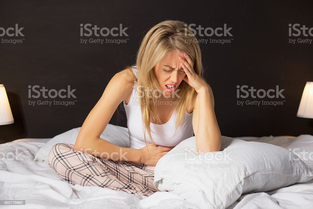 Woman in pain sitting in bed stock photo