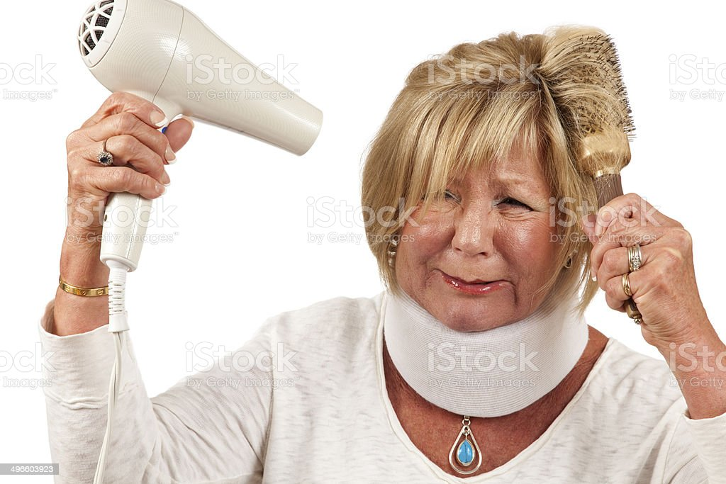Woman in pain with neck brace trying to dry hair royalty-free stock photo