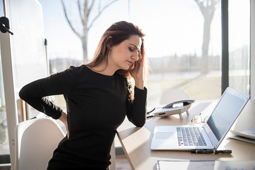 istock Woman in pain working in the office 898357594