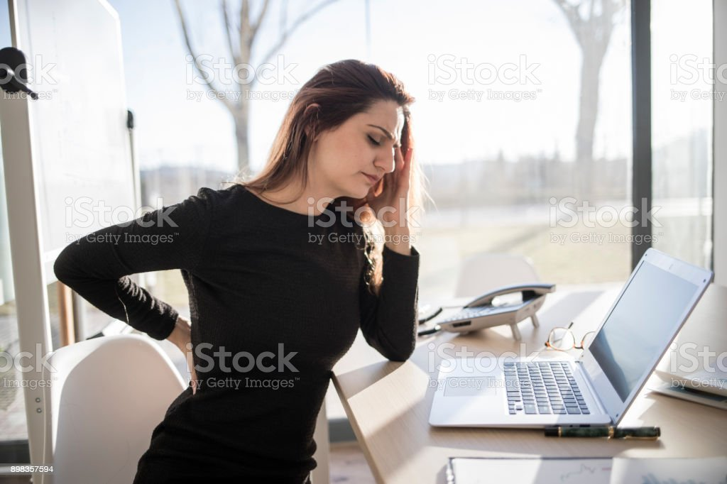 Woman in pain working in the office stock photo