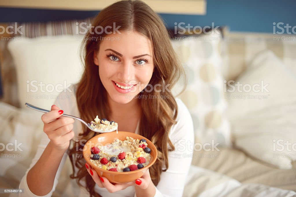 woman in pajamas in bedroom eating muesli with berries stock photo