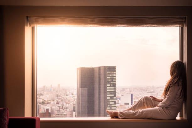 Woman in pajamas looks out of hotel window in Shibuya, Tokyo, Japan stock photo
