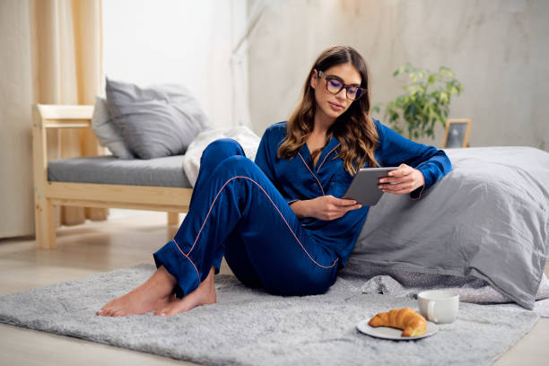 Woman in pajamas sitting on the floor in bedroom and using tablet. stock photo