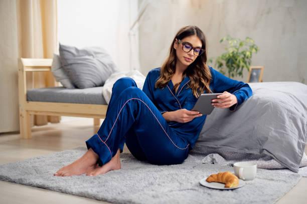 Frau in Pyjamas sitzen auf dem Boden im Schlafzimmer und mit Tablet. – Foto