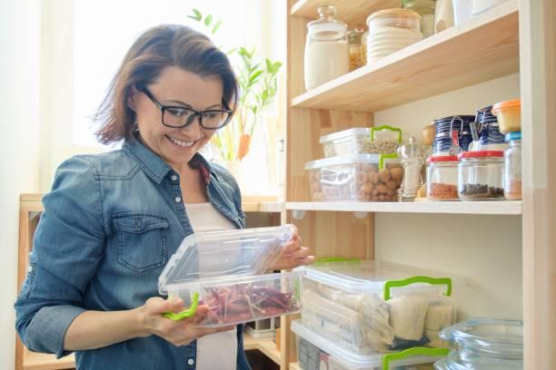 Mujer en recipiente de sujeción de despensa con ají amargo rojo. Armario de almacenamiento en cocina - foto de stock