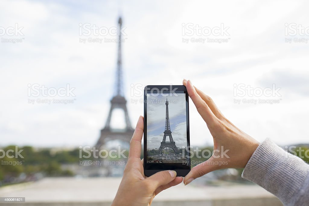 Woman in Paris taking pictures front of Eiffel Tower, Phone royalty-free stock photo