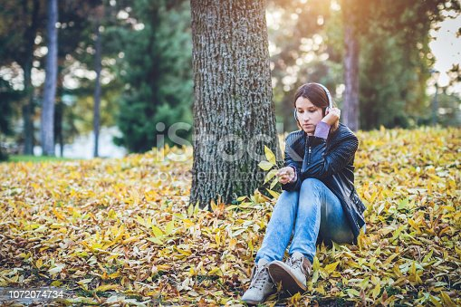 Woman in park sitting on ground listening music and relaxing in autumn day.