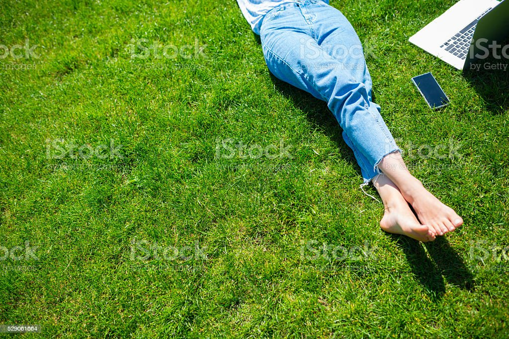 Woman in park taking a break from working on laptop stock photo