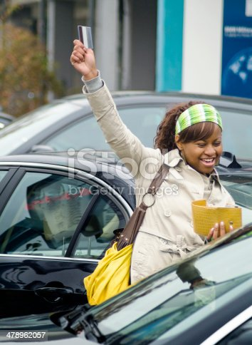 173607342 istock photo Woman in parking lot smiling with credit card 478962057