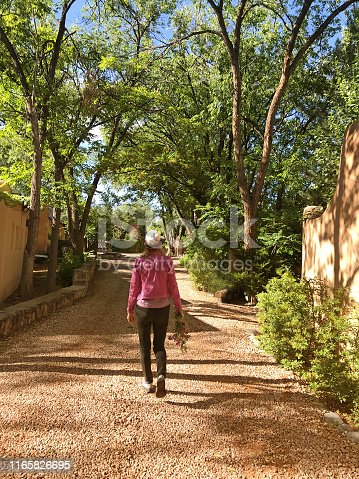 Woman in hat and pink jacket walking with a bouquet of wild flowers. Shot in Santa Fe, NM in early morning.