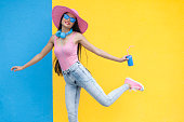 istock Woman in pink outfit holding blue can and dancing 875944608