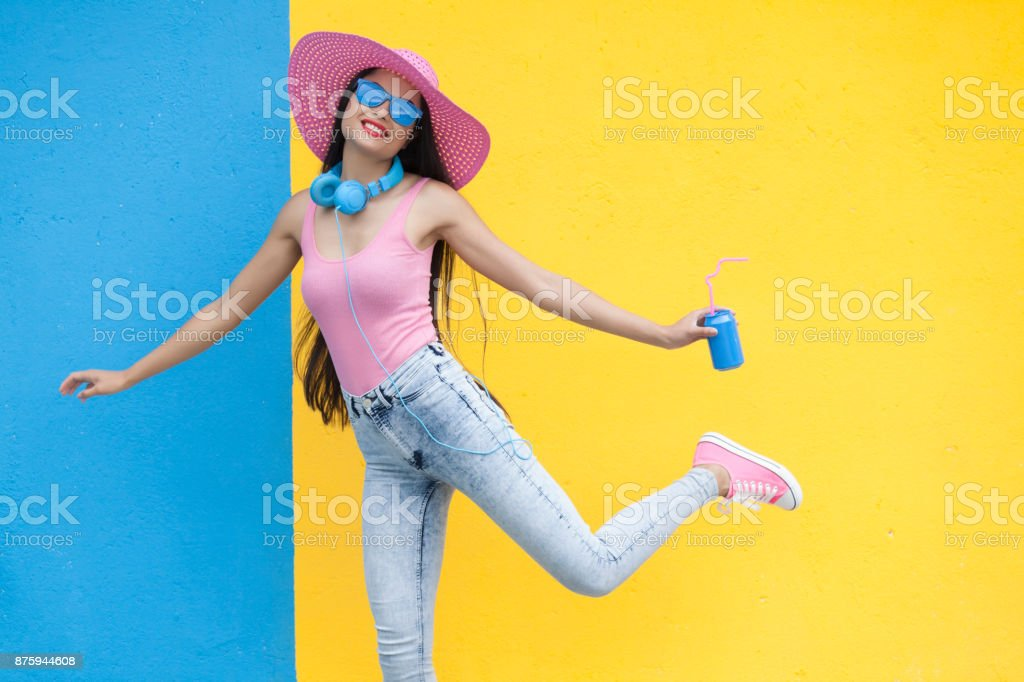 Woman in pink outfit holding blue can and dancing stock photo