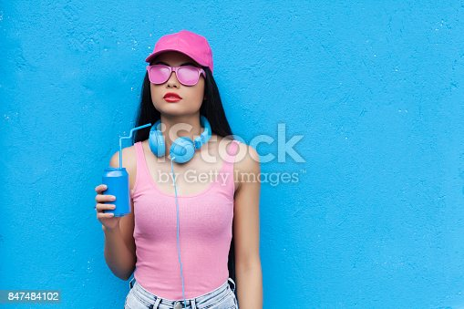 istock Woman in pink outfit holding blue can 847484102