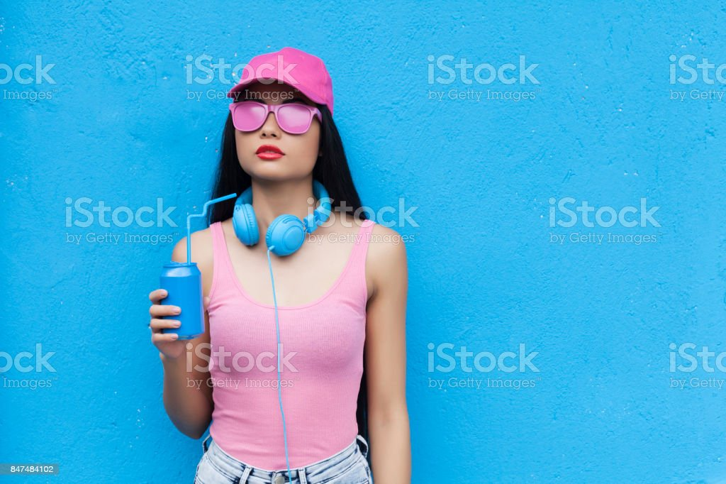 Woman in pink outfit holding blue can stock photo