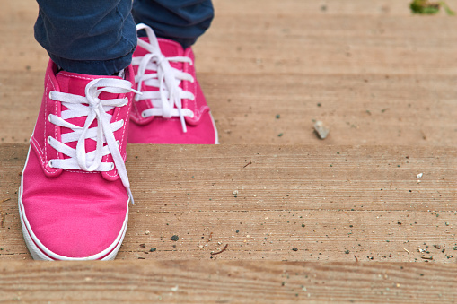 Woman in pink / purple canvas vintage shoes and blue jeans.