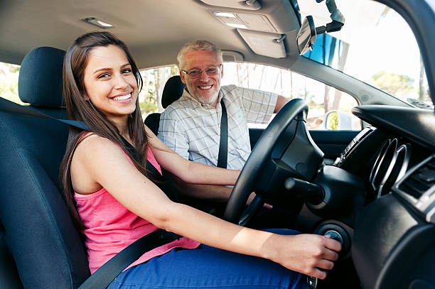Woman in pink shirt learning to drive Learner driver girl with instructor taking lessons driving instructor stock pictures, royalty-free photos & images