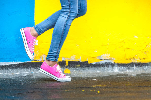 Woman in pink sneakers Woman in pink sneakers against yellow and blue wall saturated color stock pictures, royalty-free photos & images