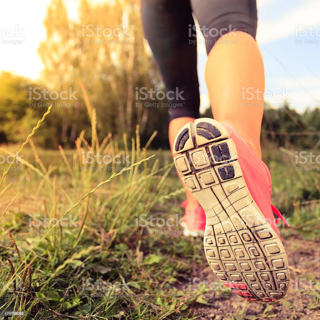 A woman in pink sneakers runs outdoors stock photo