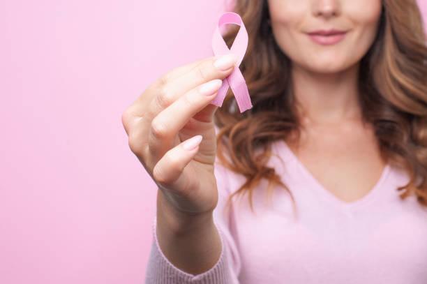 mulher de suéter rosa com fita rosa apoiando campanha de conscientização sobre o câncer de mama - outubro rosa - fotografias e filmes do acervo