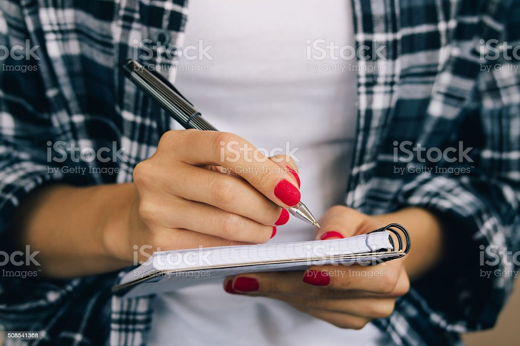 Woman in plaid shirt and a red manicure pen writing stock photo