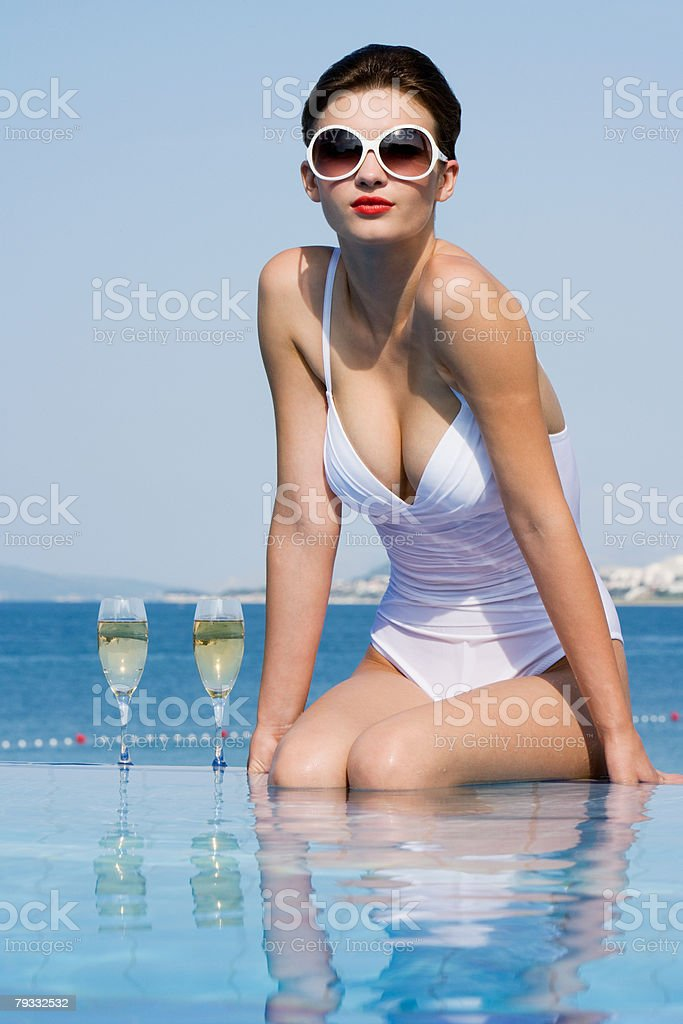 Woman in pool with champagne 免版稅 stock photo