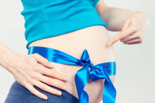 Woman in pregnant with blue ribbon on belly, concept of expecting for boy stock photo