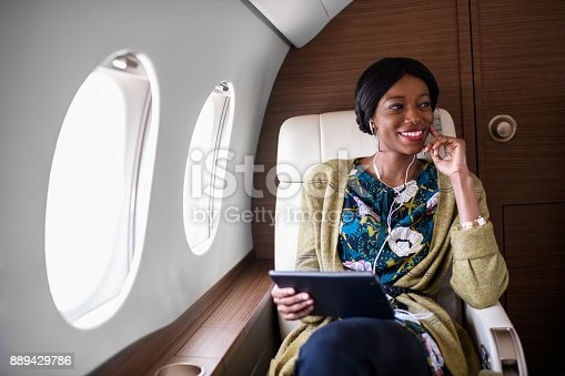 Black woman sitting inside private jet airplane and holding digital tablet.