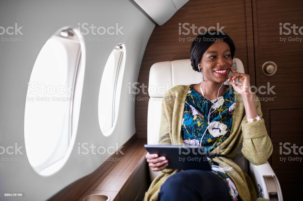 Woman in private jet airplane stock photo