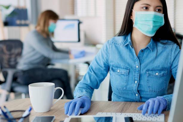 Frau in Schutzhandschuhen und Maske im Büro – Foto