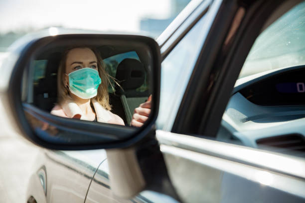Woman in protective mask driving a car on road. Woman in protective mask driving a car on road. Safe traveling. driver occupation stock pictures, royalty-free photos & images
