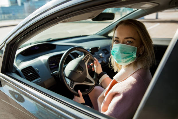 Woman in protective mask driving a car on road. stock photo