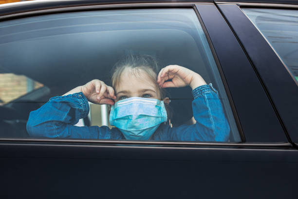 Woman in protective mask driving a car on road