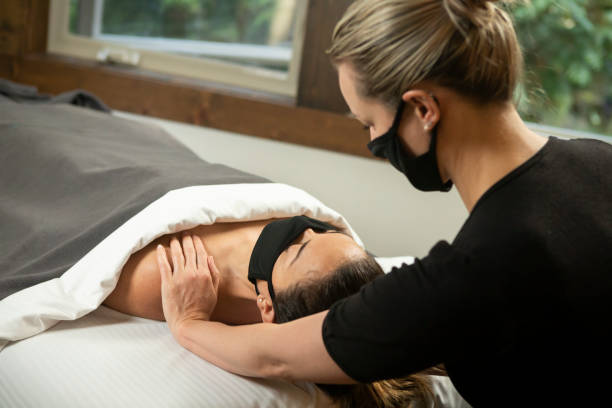 Woman in protective mask having massage treatment.