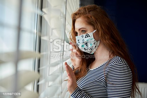 Woman in protective mask next to the window