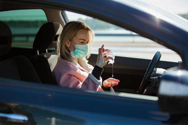 vrouw in beschermende maskerzitting in een auto op weg, gebruikend handontsmettingsmiddel. - mirror mask stockfoto's en -beelden