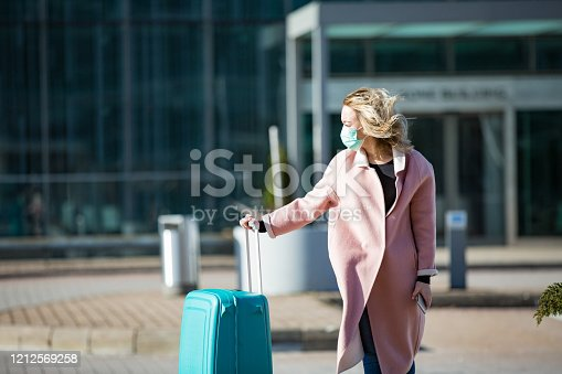 Woman in protective mask standing at airport entrance with smartphone and big luggage case, browsing, texting, using mobile app. Safe traveling.
