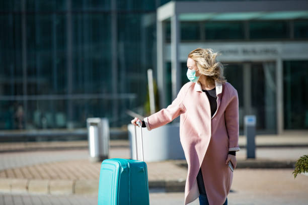 Woman in protective mask standing at airport entrance with smartphone and big luggage case stock photo