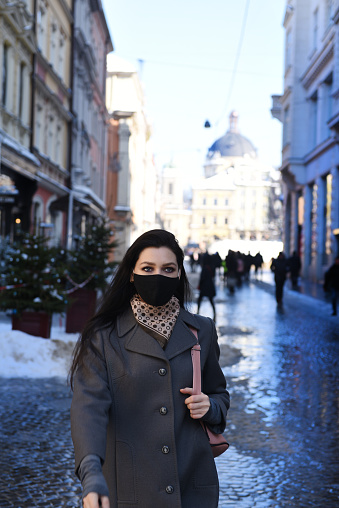 Woman in protective mask walking in the old Town.