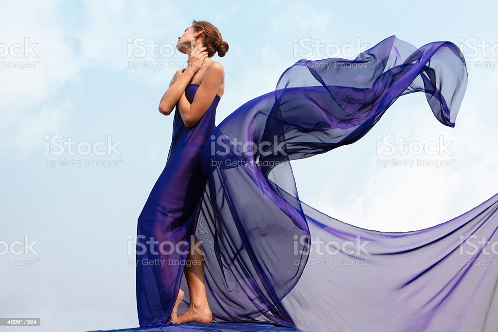 Woman in purple shawl dress blowing behind her stock photo