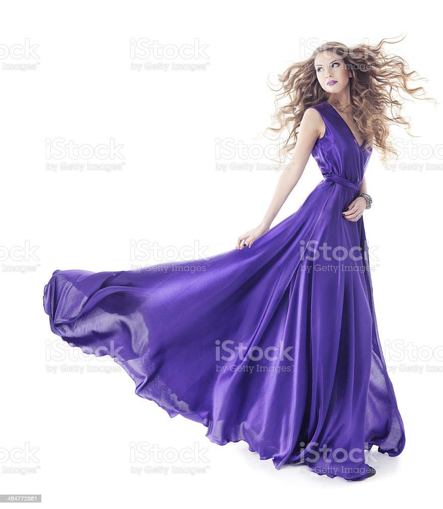 Woman in purple silk dress walking over white stock photo