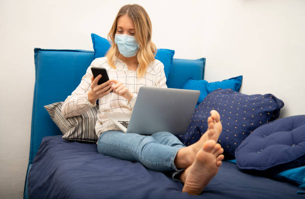 Woman in quarantine for Corona virus wearing protective mask and smart working on sofa at home stock photo